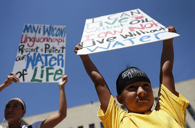Seven-year-old Omaka Nawicakinciji (R) of the Oglala Lakota Nation in South Dakota participates with his mother Heather Mendoza (L) during a rally on Dakota Access Pipeline August 24, 2016, outside U.S. District Court in Washington, D.C.