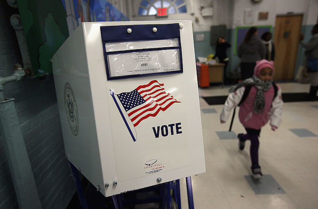 White voting booth stands in school hallway, child runs past