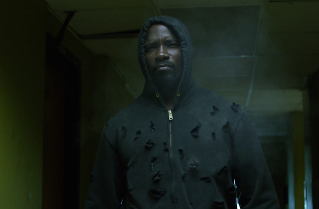 Black man in black hoodie with bullet holes against green wall