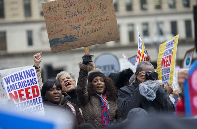 Three black women in brown coats holding signs and a raised fist next to Black man in navy coat with black camera against brown background