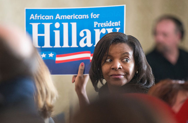 Black woman holding blue campaign sign with white text and red, white and blue flag in front of beige wall