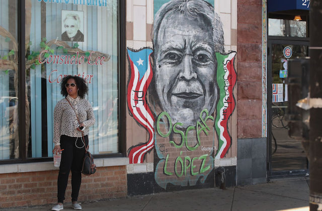 Brown woman in black-and-white shirt and black pants stands next to grey, red, white, blue and green mural with green text on red brick wall