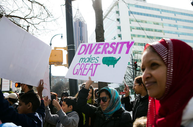 "Women in hijab, one holds sign that reads: ""Diversity makes American great."""