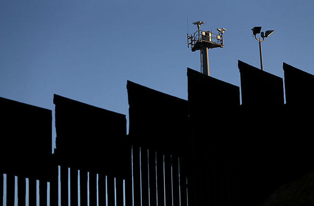 Surveillance cameras stand above the U.S.-Mexican border fence at Playas de Tijuana on January 27, 2017, in Tijuana, Mexico.