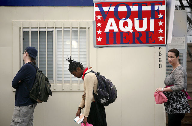 People stand in line to vote, Black person in center