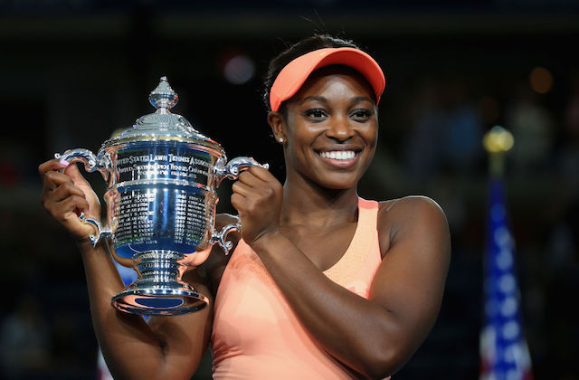 Black woman in peach-colored tennis outfit holds silver trophy in front of blurry black background