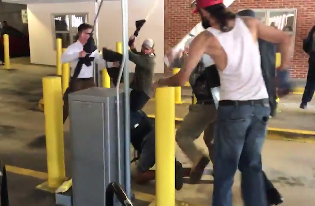 People surround Black 20-year-old on ground of parking garage, weapons in hand