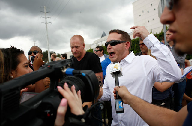 Black and Brown and White people in multicolored clothing holding black microphones and video cameras surround White men in black t-shirt and white dress shirt in front of grey sky