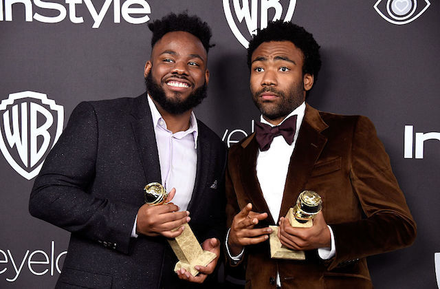 Black man in black tuxedo holds gold statue next to Black man in brown tuxedo holding gold statue in front of grey screen with white text and insignia