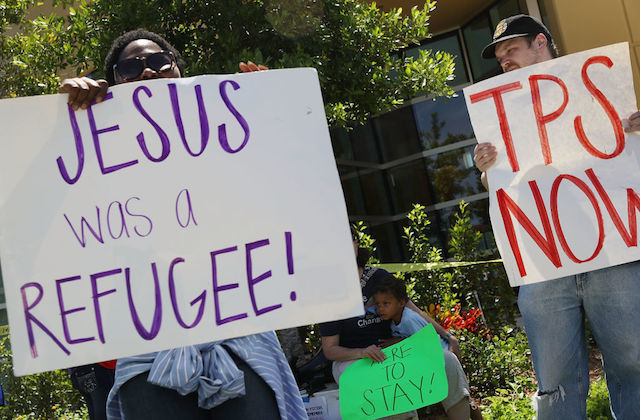 "Protesters hold signs. One says, ""Jesus was a refugee!"""