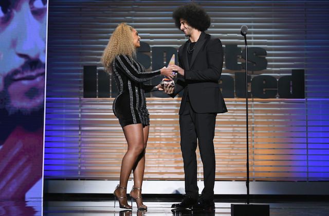 Black woman with blond hair in black dress passes silver grey award statue to Black man in black suit in front of brown screen on black stage
