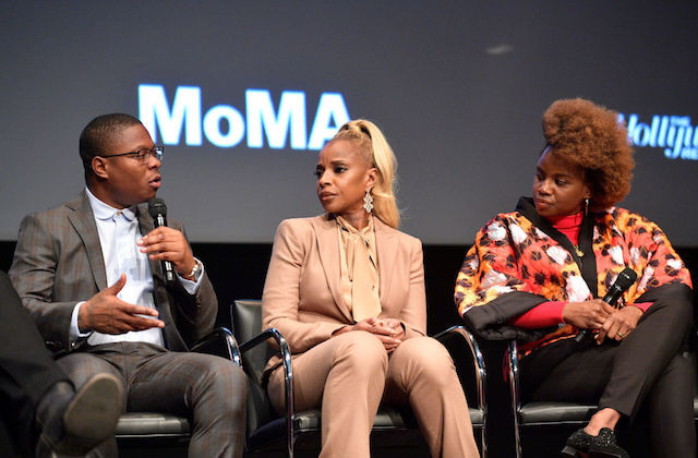 Black man in grey and brown plaid suit holds black microphone and sits next to Black woman in beige outfit and Black woman in black pants and red and black and orange blouse in front of dark grey screen