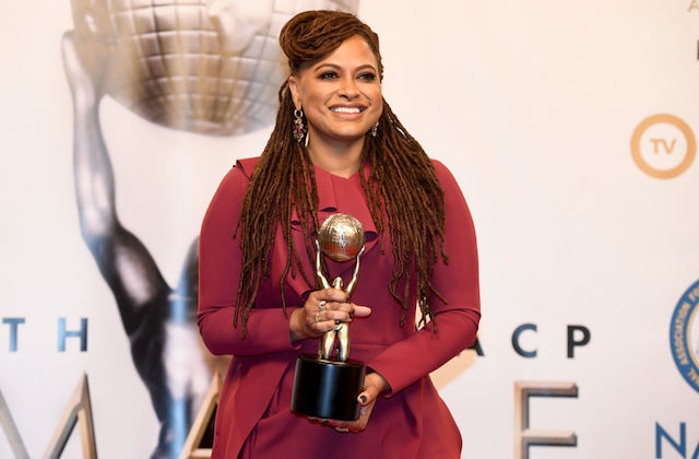 Black woman in pink dress smiles while holding gold award statue in front of beige background with black and gold text