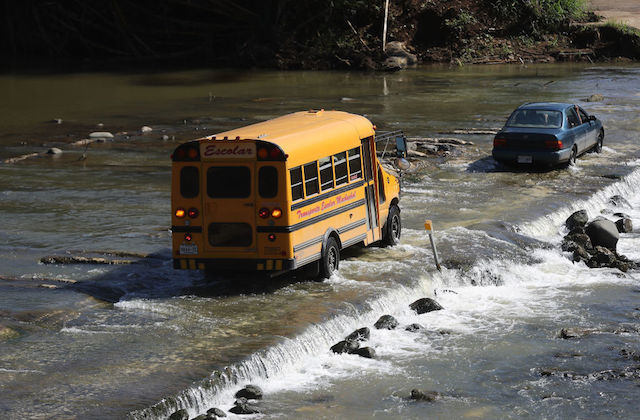 A school bus crosses a makeshift automobile bridge, after the original bridge was washed away during Hurricane Maria flooding, on December 20, 2017 in Morovis, Puerto Rico.