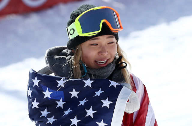 Asian girl with blonde hair wearing grey hat and yellow and orange goggles and grey hoodie while wrapped in red and white and blue U.S. flag smiles in front of red wall and white snow