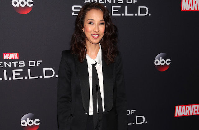 Asian woman in black suit with black tie and white shirt smiles in front of dark grey wall with white text and red and white insignia