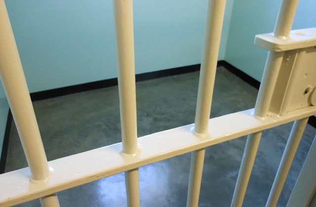 Yellow-painted prison bars, blue walls, gray floors.