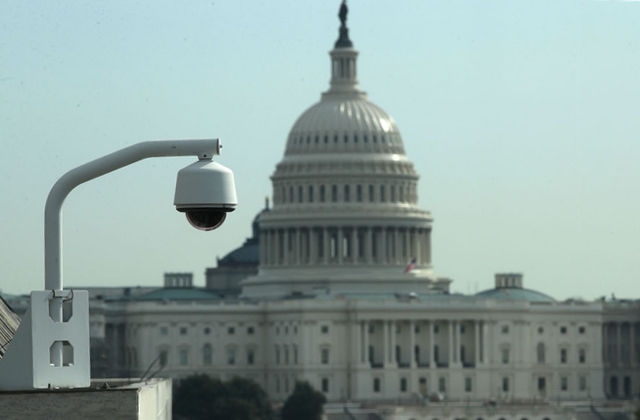 White surveillance camera in the foreground, U.S. Capitol in the background
