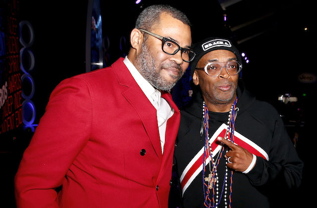 Black man in red blazer and white shirt stands next to black man in black hat with white text and black jacket with red and white stripes in front of dark blue and black stage