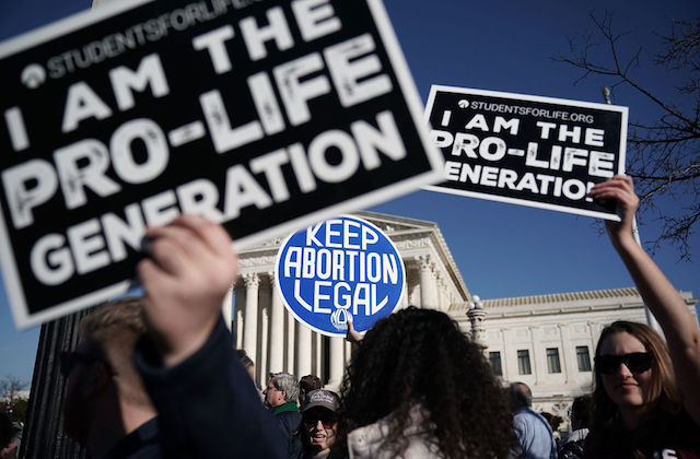 "Two protestors holding black signs with white font that say ""i am the pro-life generation"" attempt to block a blue sign with white font that says ""keep abortion legal"" at a rally outside the supreme court"