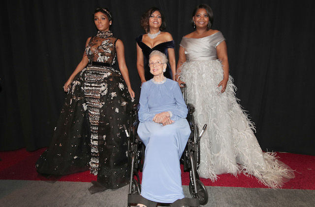 Black woman in blue dress and wheelchair sits in front of Black women in black and grey dresses in front of black curtain