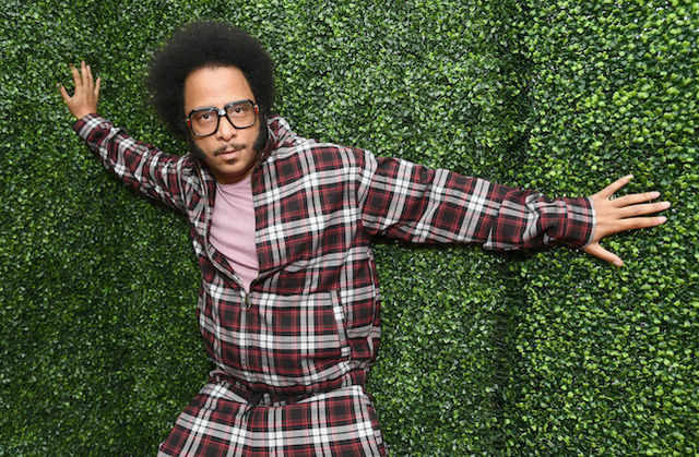 Boots Riley with black afro and glasses and beard in red plaid suit and pink shirt in front of green bush