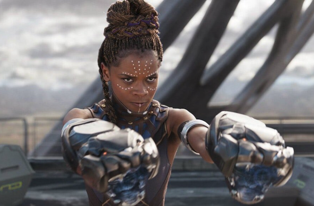 Letitia Wright in grey and brown warrior outfit with panther-shaped arm cannons in front of grey structure
