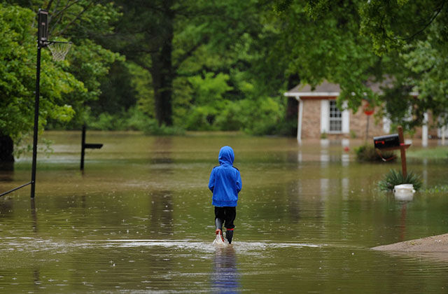 A child walks in his flooded neighborhood on May 4, 2017, in Arnold, Missouri. Towns along the Meramec River braced for the river to crest after days of rainfall in the region.