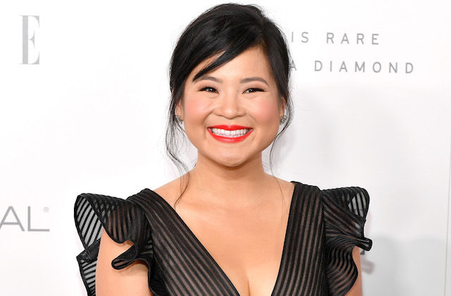Kellie Marie Tran smiles in black dress in front of white wall with grey text