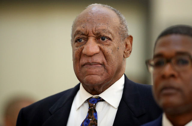BIll Cosby and Andrew Wyatt. Black man in dark navy suit and blue and brown tie stands behind Black man in blue suit and black glasses in front of beige wall