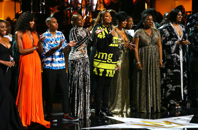 Ledisi, Naomi Campbell, Lena Waithe, Mary J. Blige, Queen Latifah, Beverly Bond and Tarana Burke stand next to one another in clothing of different colors on black stage in front of black and orange background