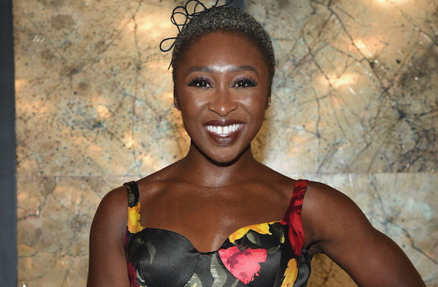 Cynthia Erivo in black and orange and pink dress in front of brown wall