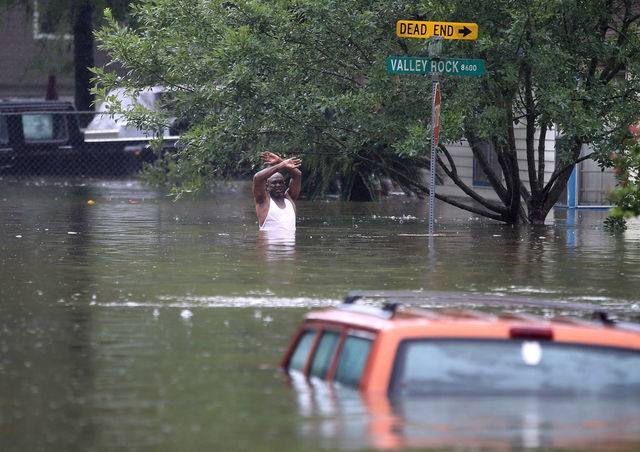 A man waves down to rescue crew as he tries to leave the area after he was inundated with flooding from Hurricane Harvey on August 28, 2017 in Houston, Texas.
