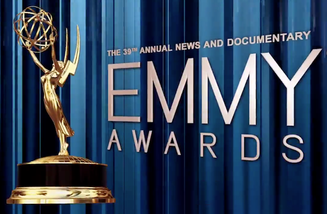 Gold text and Emmy award statue on blue curtain