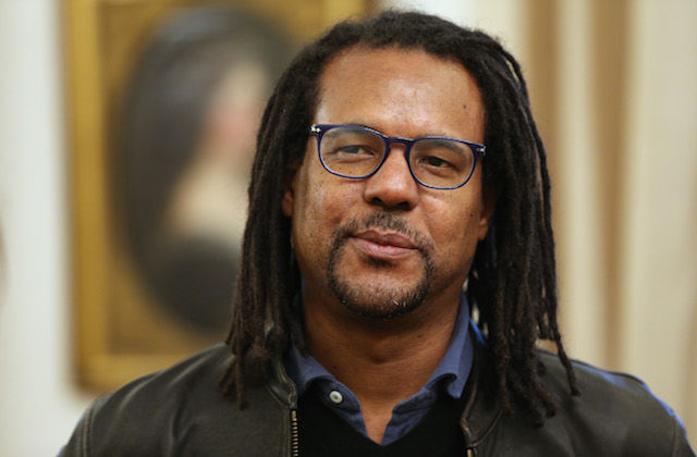 Colson Whitehead. Black man with black dredlocs and glasses in navy shirt and black jacket in front of beige and black painting in gold frame on beige wall