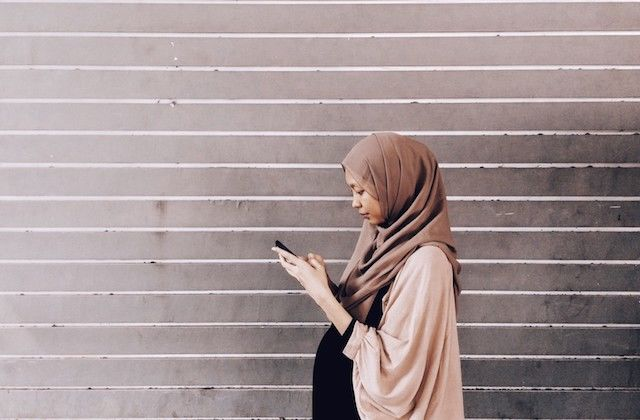 Light brown hijabi woman wears taupe headscarf, tan sweater and black dress, looks down at cell phone in her hands