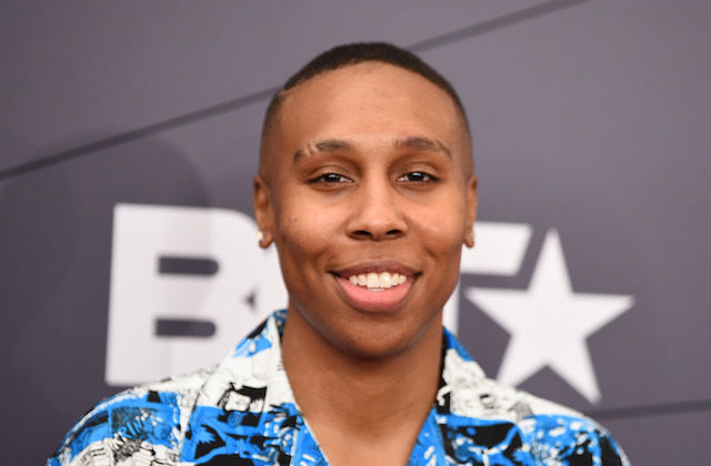 Lena Waithe. Black woman with short hair smiles in blue patterned shirt in front of grey wall with white text