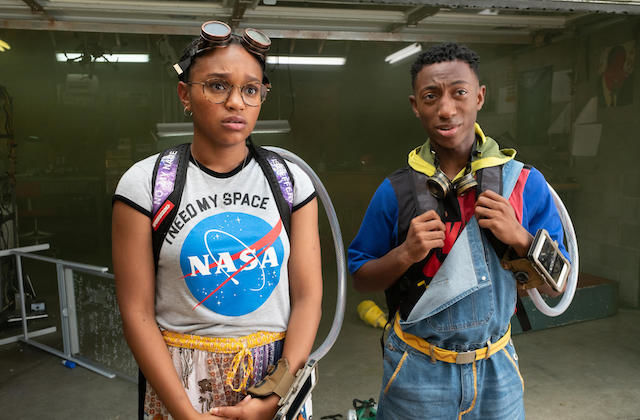 Eden Duncan-Smith and Danté Crichlow. Black girls in white shirt with red and white and blue NASA logo stands next to Black boy in blue and red and grey and yellow jacket in front of grey walls
