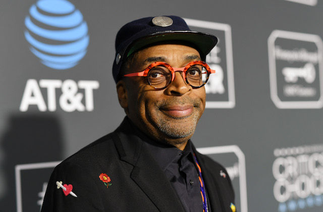 "Spike Lee. Black man in black hat and black and red glasses and suit smiles in front of grey wall with light grey images and blue logo and white text spelling ""AT&T"""