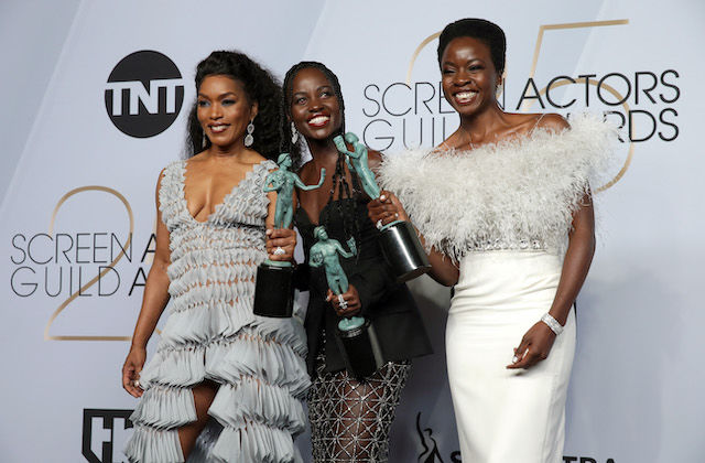 Angela Bassett, Lupita Nyong'o and Danai Gurira. Three Black women in grey, black and white dresses smile while holding green award statues in front of grey background with black text.
