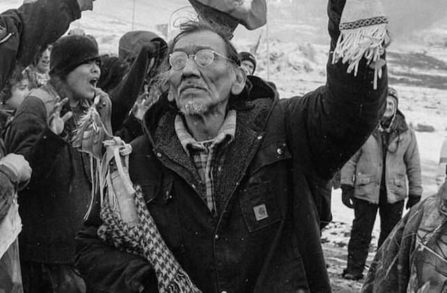 Nathan Phillips. Black-and-white photograph of Indigenous man holding feather and other articles while wearing black jacket and glasses and surrounded by people in dark clothing
