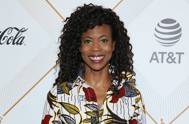 Hannah Beachler. Black woman with black hair smiles while wearing white dress with red and gray and yellow leaves and black lines in front of grey background with orange lines and grey CocaCola and AT&T logos.