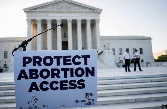 U.S. Supreme Court and protest sign supporting abortion
