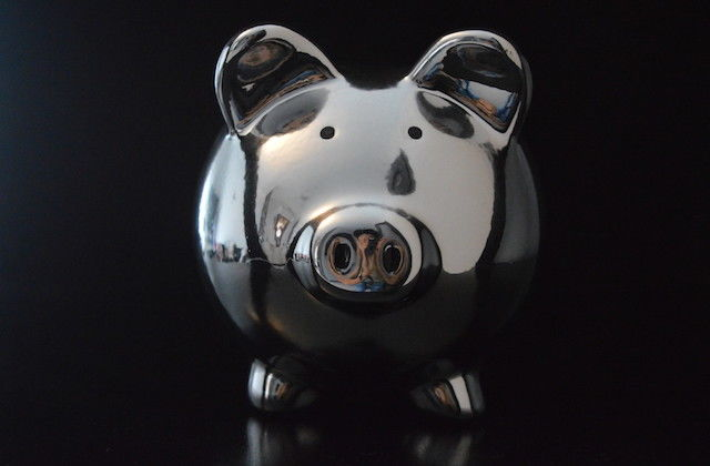 Silver piggy bank on black background