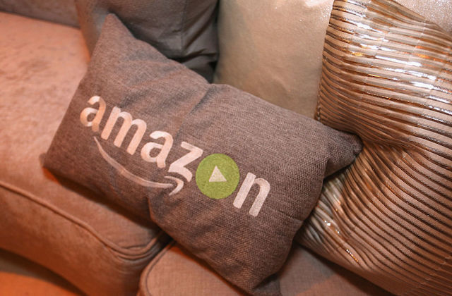 "A gold pillow that reads ""Amazon,"" on a couch with other similarly hued  pillows around."