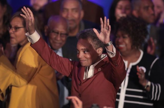Lori Lightfoot. A Black woman with short hair stands with her hands up whle wearing a red blazer and white shirt. She is surrounded by celebrating Black people.