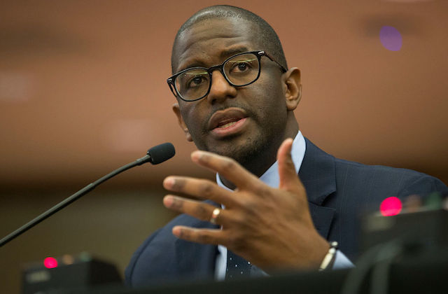 Andrew Gillum. A Black man wearing a dark suit and black-rimmed eyeglasses.