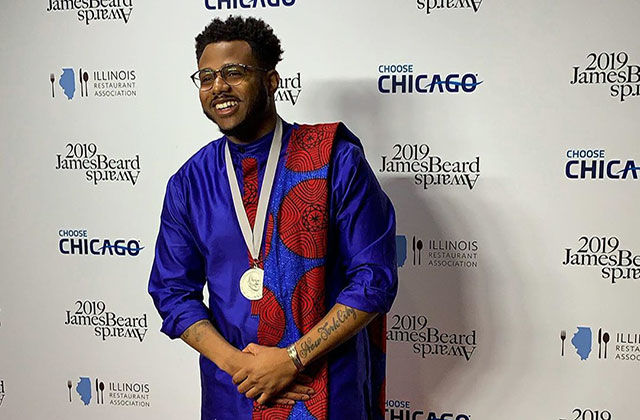 Kwame Onwuachi. Black man in front of step and repeat wearing blue African top, gold chain, with red and blue African scarf over shoulder.