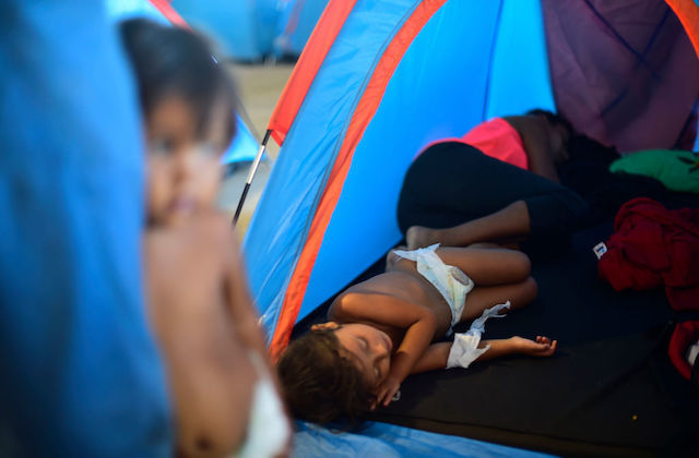 Small child wearing diapers and family members sleep in blue and orange tent