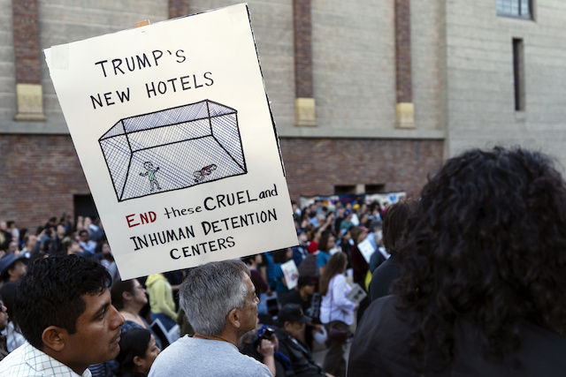 "A demonstrator holds up a hand drawn sign of an immigration cage with the caption ""Trump's new hotels."""